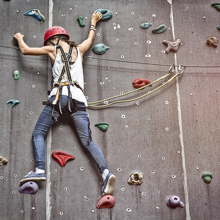 Girl with safety climbing gear on climbing wall