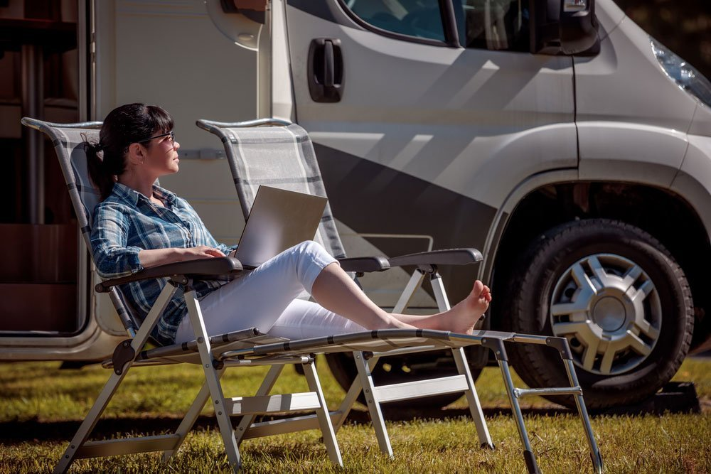 Woman camping at RV Park with Laptop