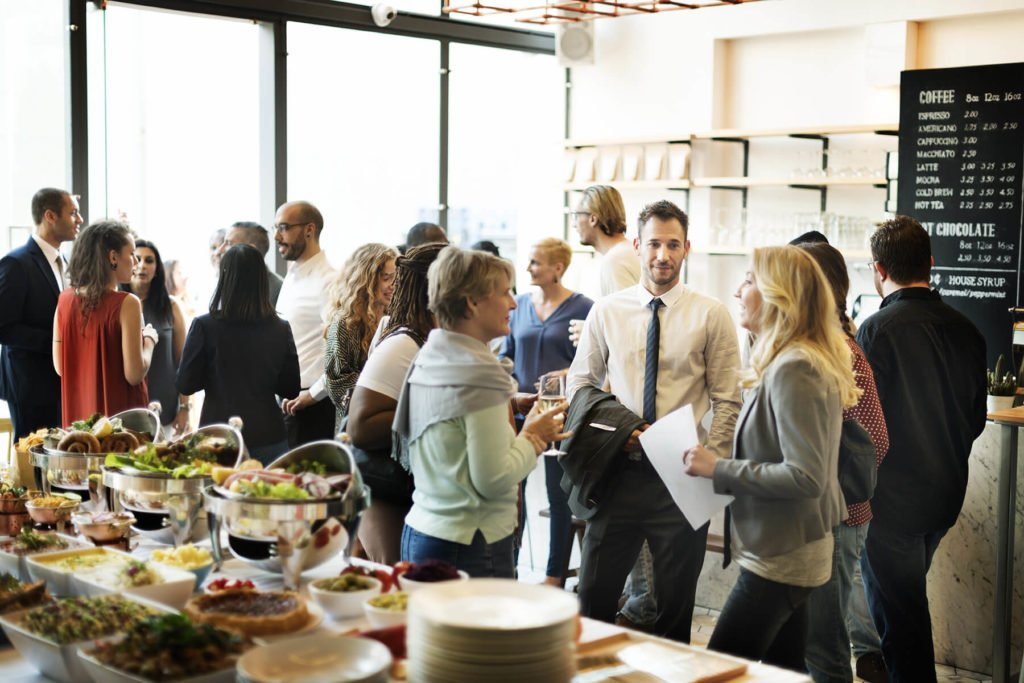 Group of people gathered in an event space enjoying food.