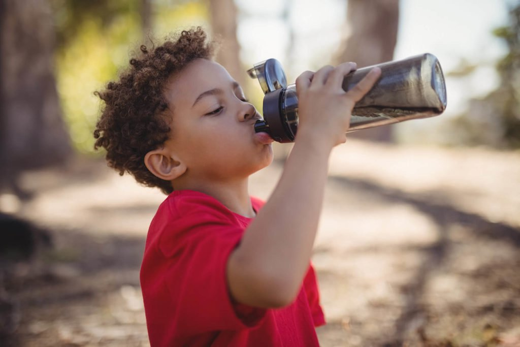 Young boy drinking from a water bottle