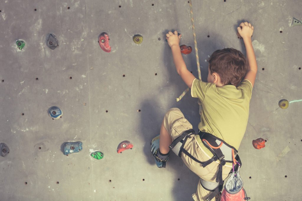 Little boy climbing on rock wall