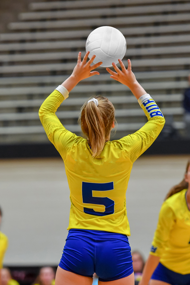 Girl setting a volleyball during a game on a volleyball court